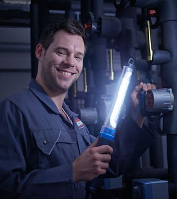 An LED work lamp helps a man to see more clearly while he is fixing a car